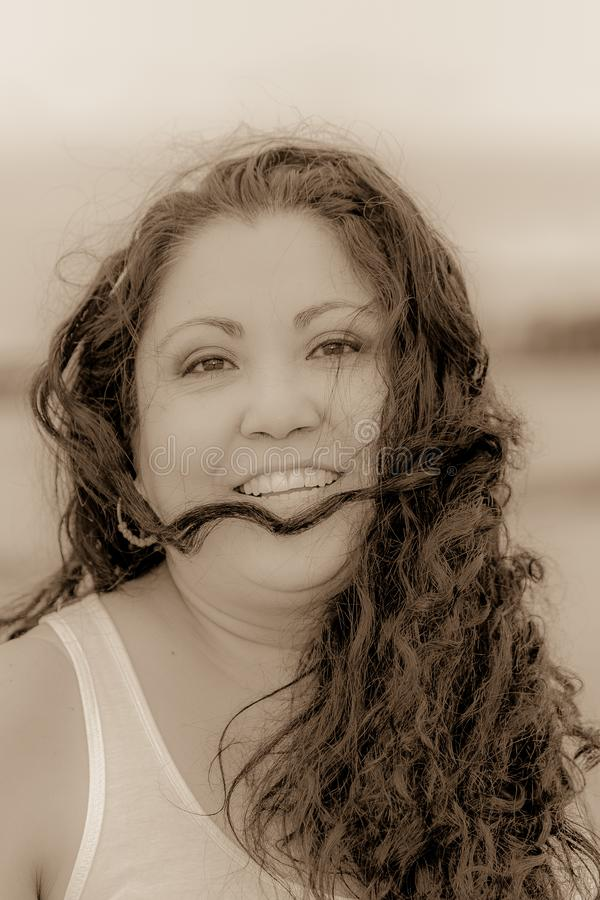 Beautiful black and white image of a happy smiling Mexican woman with long hair tousled by the wind stock image