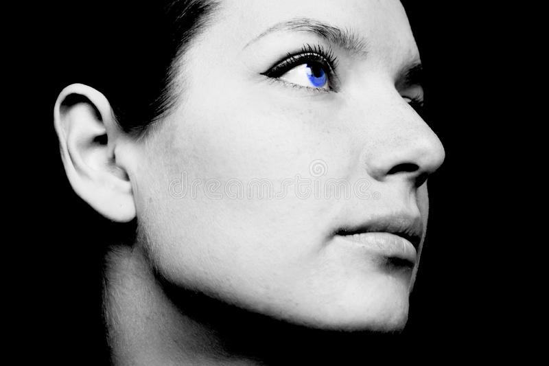 Black and white photo of a woman`s face with blue eyes royalty free stock image