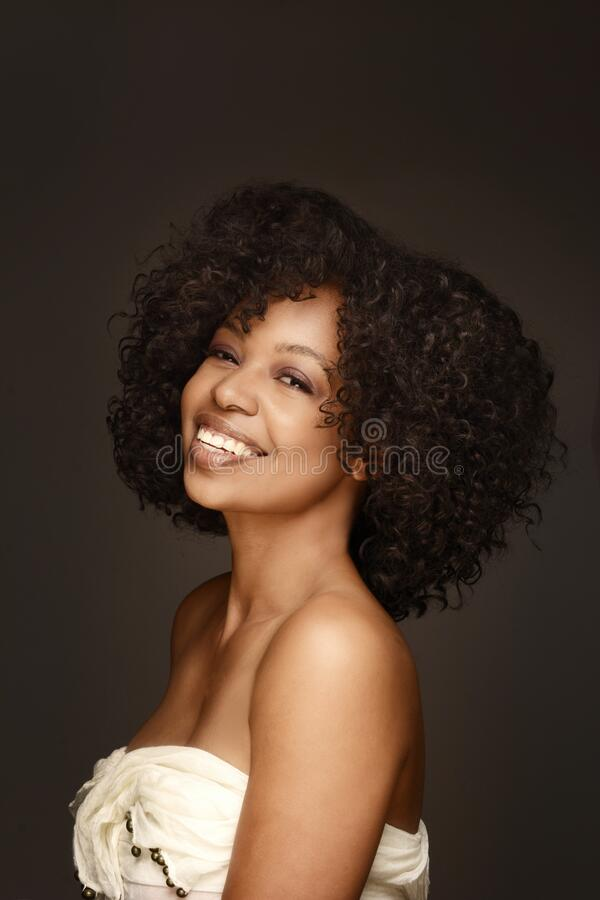 Beautiful Black woman with amazing curly hair and golden glowing skin royalty free stock photography