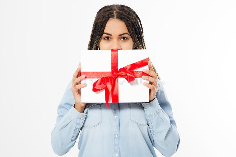 Beautiful black woman hides her face behind a gift box on a white background royalty free stock photo