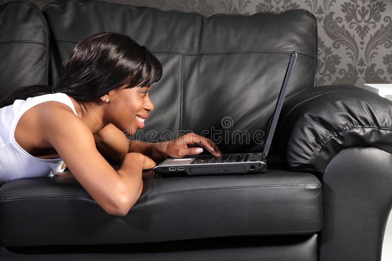 Beautiful black woman at home using facebook. Beautiful smiling young african american woman lying on black leather sofa at home, surfing facebook on the stock photography