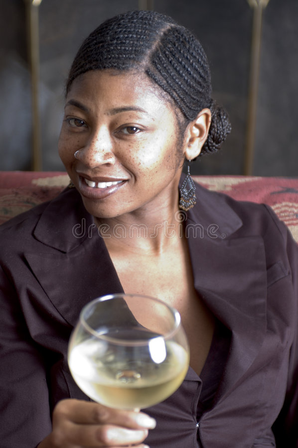 Beautiful black woman on sofa. Beautiful black women great smile glass of wine stock photography