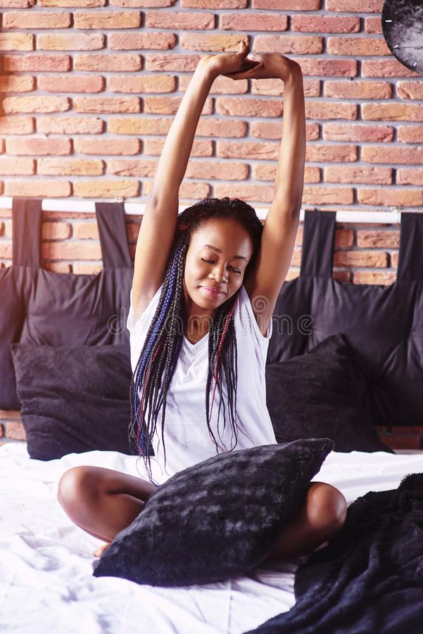 Beautiful black woman waking up in her bed, she is smiling and stretching.  stock image