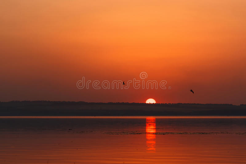 Beautiful blazing sunset landscape at the river Dnipro and orange sky above it with awesome sun golden reflection on calm water. As a background. Amazing summer royalty free stock images
