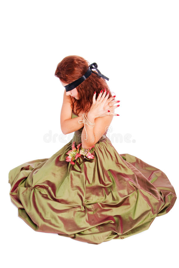 Beautiful blindfolded girl in dress. Picture of a beautiful blindfolded girl in dress on floor stock image