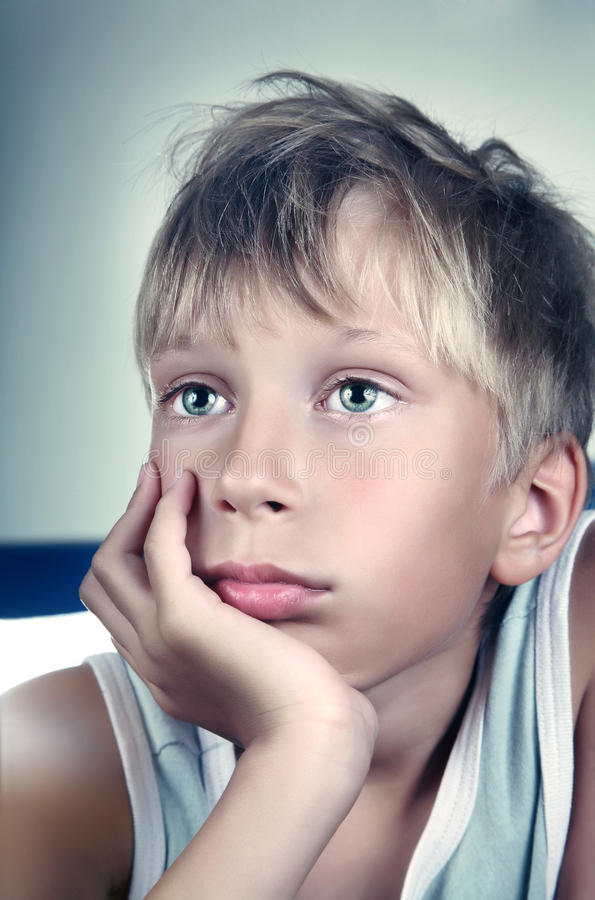 Beautiful blond boy wearing a green undershirt dreaming and looking sad royalty free stock photography