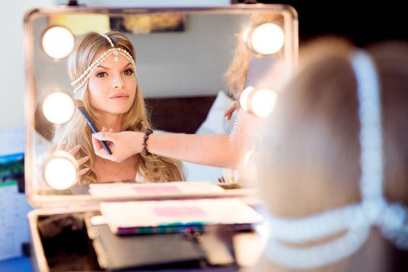 Beautiful blond bride doing makeup in her wedding day near mirror. Bride makeup. stock photo