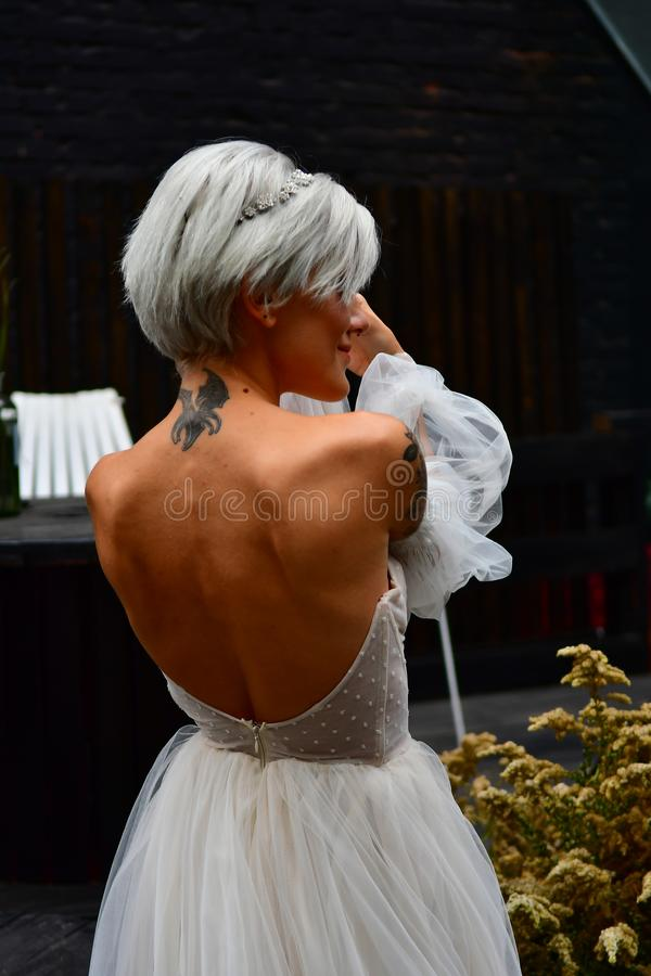 Beautiful blond bride in white dress, naked back and tatoo royalty free stock photos