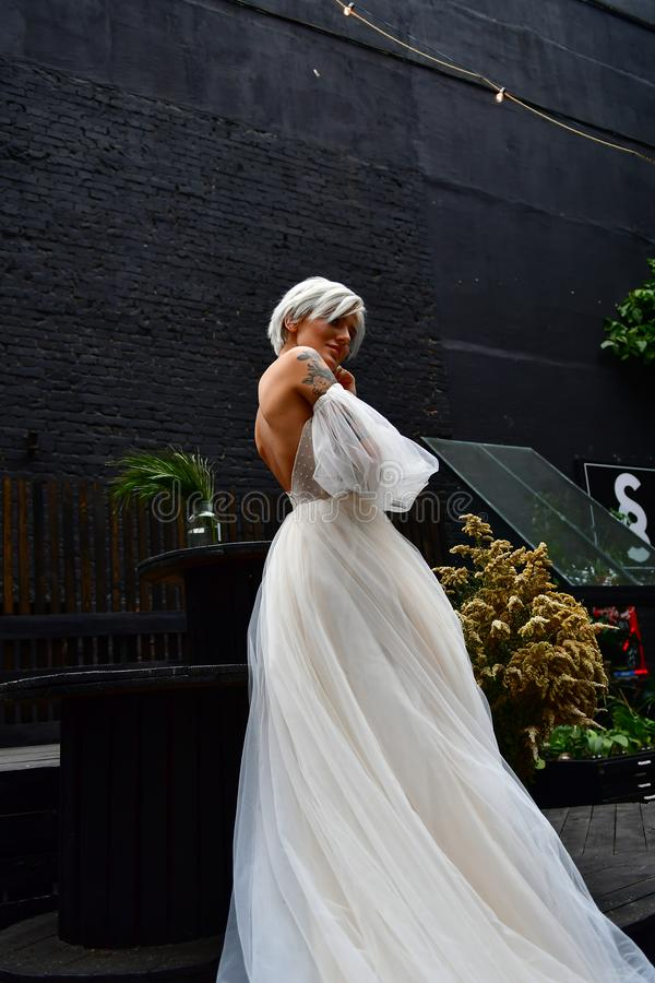 Beautiful blond bride in white dress, naked back and tatoo stock images