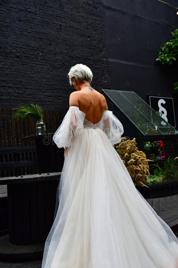 Beautiful blond bride in white dress, naked back and tatoo stock photos