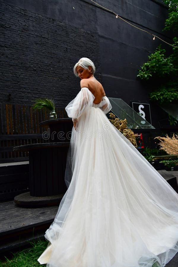 Beautiful blond bride in white dress, naked back and tatoo stock image