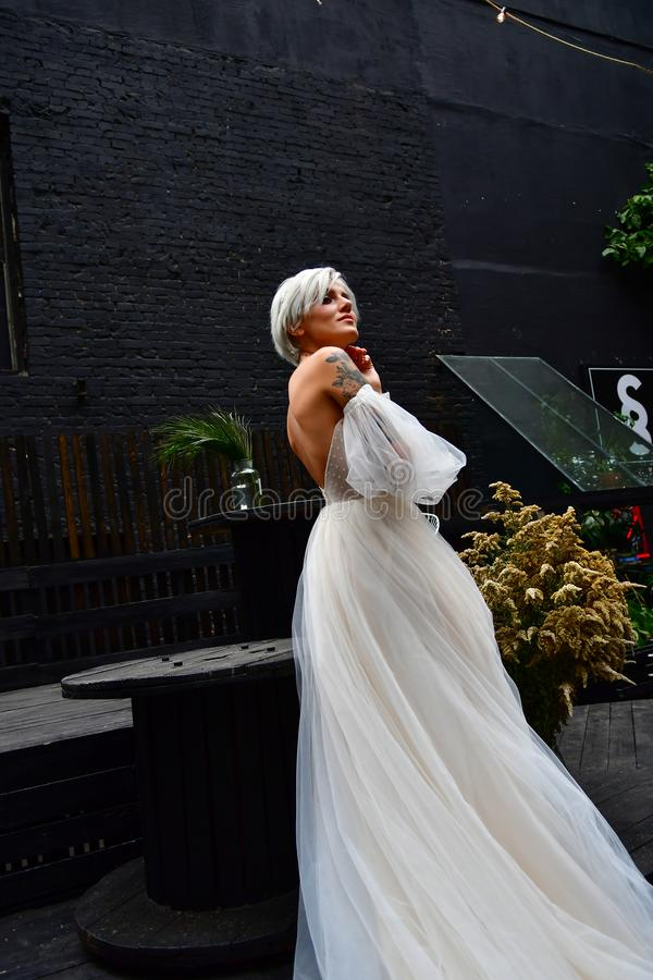 Beautiful blond bride in white dress, naked back and tatoo royalty free stock photo