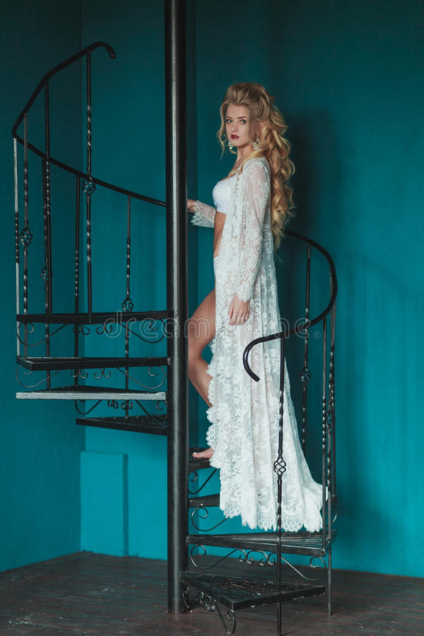 Beautiful blond bride in white negligee walking up black wrought iron staircase royalty free stock images