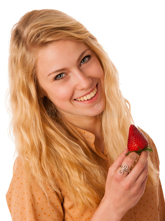 Beautiful blond cheerful caucasian woman eats a big red strawberrie isolated over white background royalty free stock images