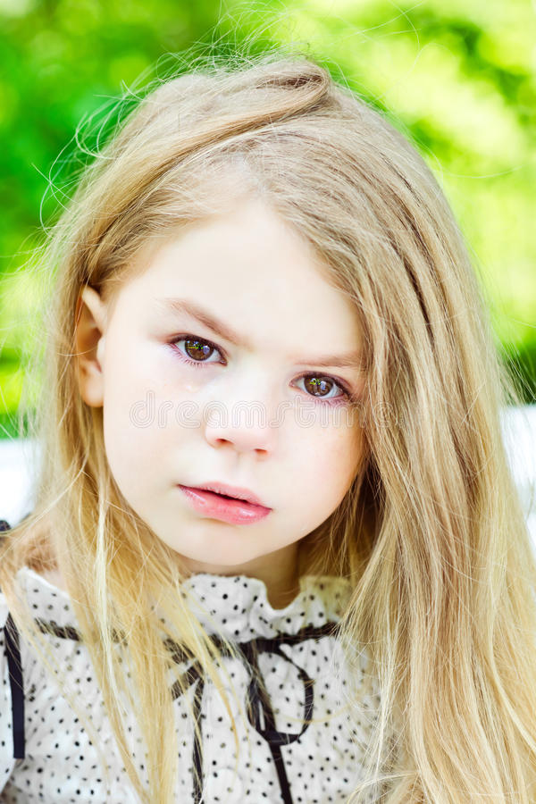 Beautiful blond crying little girl with tears on her cheeks royalty free stock photo