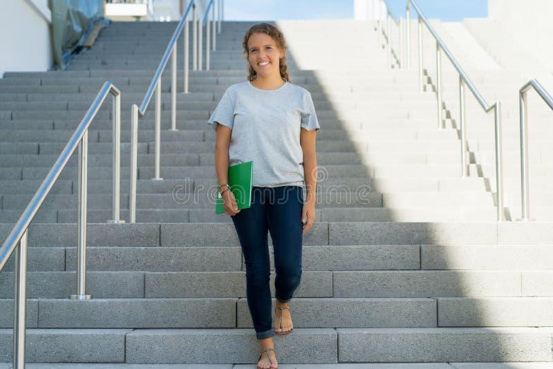 Beautiful blond female student walking to university stock photography