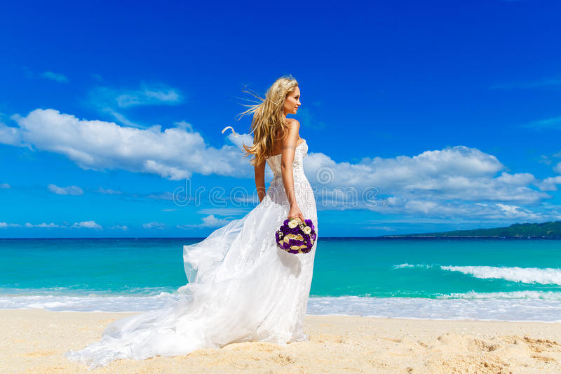 beautiful blond fiancee in white wedding dress with big long white train and with wedding bouquet stand on shore sea stock photo