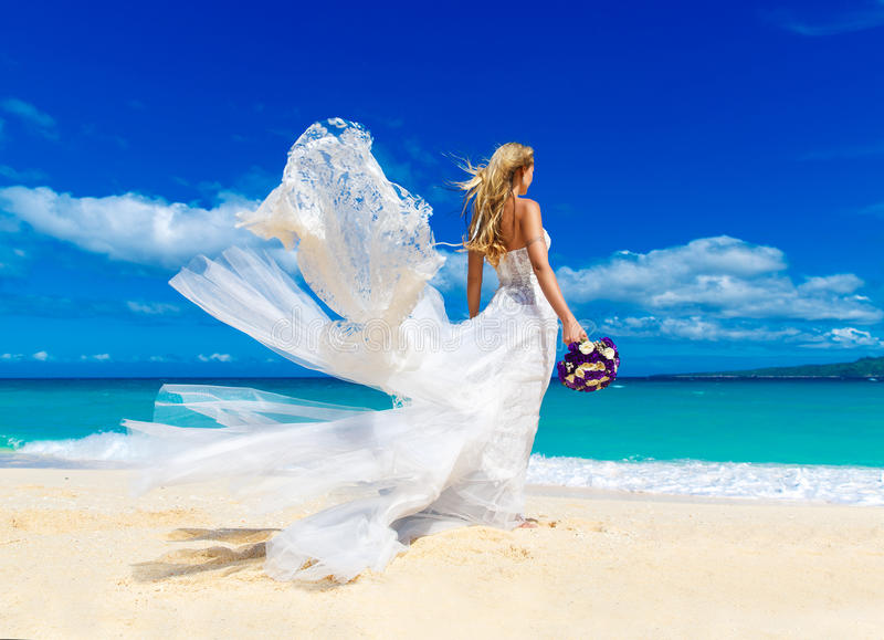 beautiful blond fiancee in white wedding dress with big long white train and with wedding bouquet stand on shore sea stock images