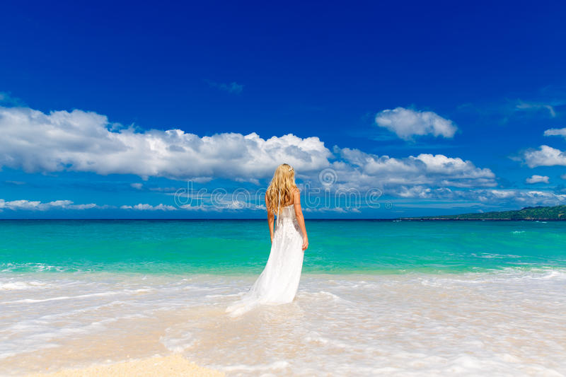 Beautiful blond fiancee in white wedding dress with big long white train stand on shore sea.  royalty free stock image