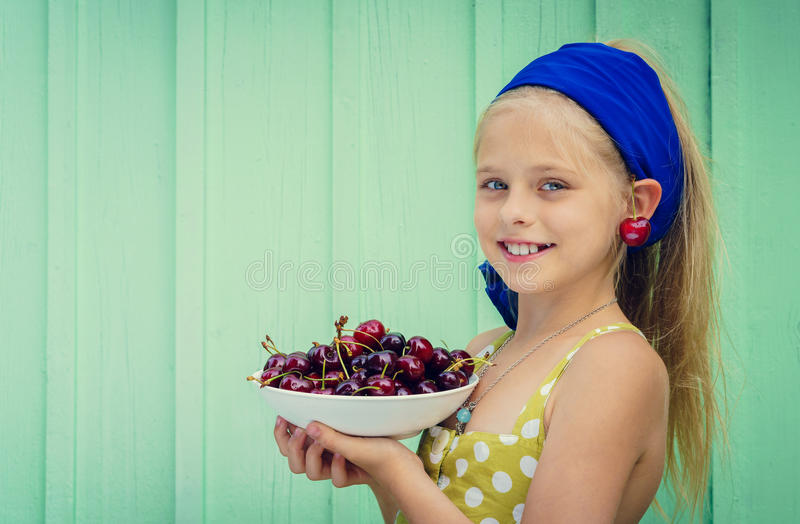 Beautiful blond girl on a background of turquoise wall holding plate with cherry. royalty free stock photography