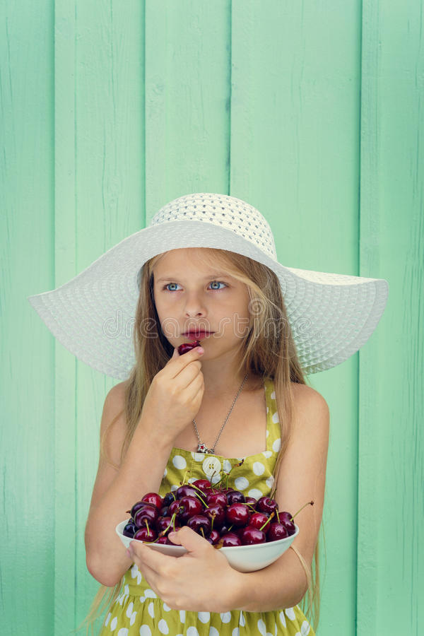Beautiful blond girl on a background of turquoise wall in the white hat holding plate with cherry. Space for text royalty free stock photography