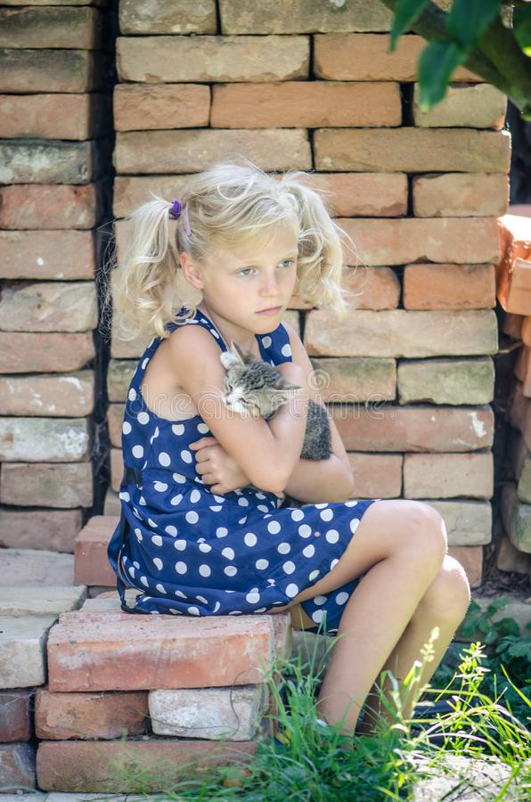 Happy child and animal cat together. Beautiful blond girl in blue dotted dress holding in arms little domestic cat while sitting in bricks royalty free stock images