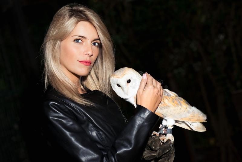 Beautiful blond girl caresses a Barn owls royalty free stock photo