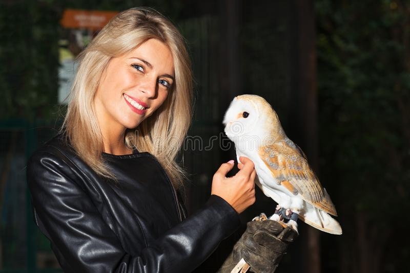 Beautiful blond girl caresses on her chest a Barn owls stock image