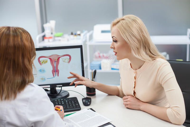 Beautiful blond girl is consulting with gynecologist. Cheerful young women is asking advice in her gynecologist. She is sitting at the desk and pointing finger stock images