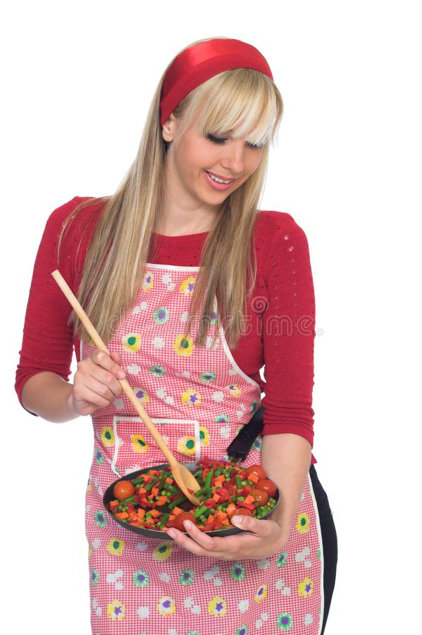 Beautiful blond girl cooking stock photography