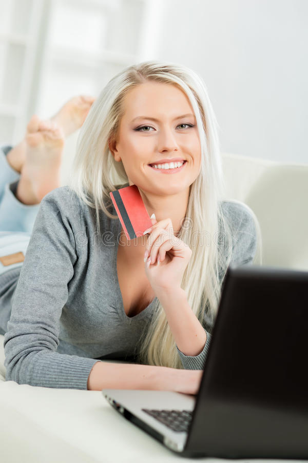 Beautiful blond girl with a credit card. Online shopping concept. Beautiful blond girl with a credit card stock image