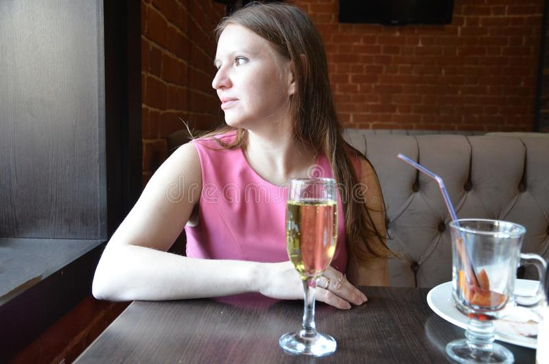 Beautiful blond girl holding a glass of champagne or wine, drinking champagne in a restaurant, in an evening pink dress royalty free stock images