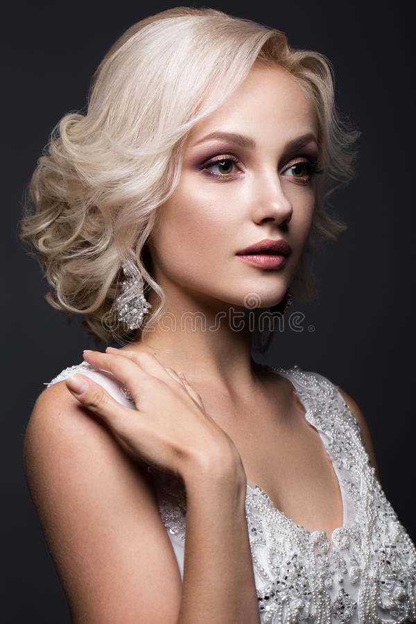 Beautiful blond girl in image of the bride with wedding accessories on her head. Beauty face. Portrait of a beautiful blond girl in image of the bride with royalty free stock images