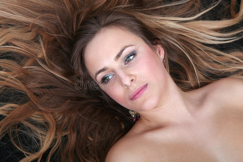 Beautiful blond girl lying on her back stock photography