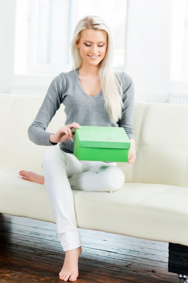 Beautiful blond girl opening a gift box. Beautiful blond girl opening a gift. Green box royalty free stock photos