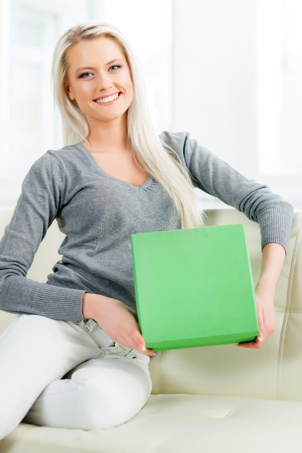 Beautiful blond girl opening a gift. Green box stock photo