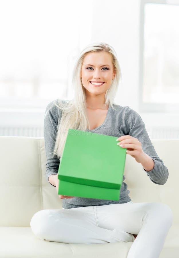 Beautiful blond girl opening a gift. Green box stock photos