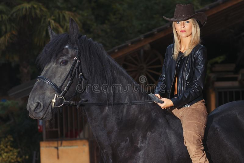 A beautiful blond girl over a black horse royalty free stock images