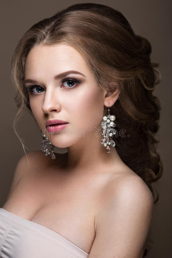 Beautiful blond girl with perfect skin, evening make-up, wedding hairstyle and accessories. Beauty face. Beautiful blond girl with perfect skin, evening make-up royalty free stock image