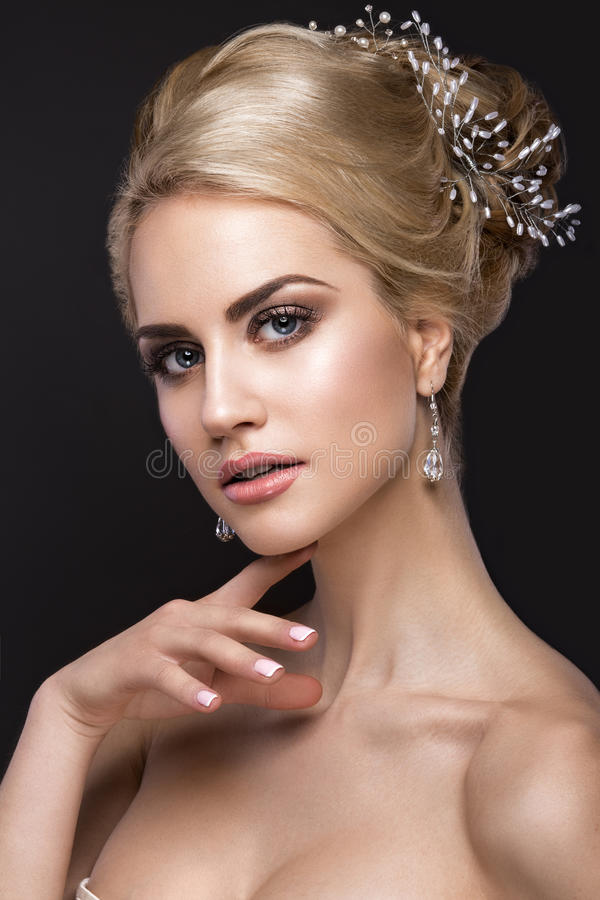 Beautiful blond girl with perfect skin, evening make-up, wedding hairstyle and accessories. Beauty face. Beautiful blond girl with perfect skin, evening make-up royalty free stock images