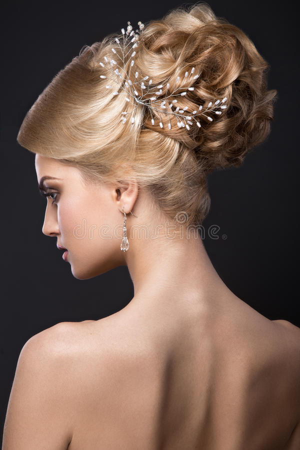 Beautiful blond girl with perfect skin, evening make-up, wedding hairstyle and accessories. Beauty face. Beautiful blond girl with perfect skin, evening make-up royalty free stock photography