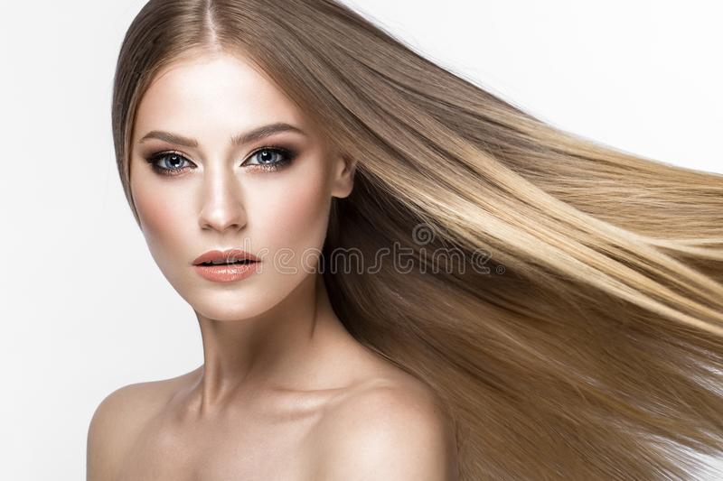 Beautiful blond girl with a perfectly smooth hair, and classic make-up. Beauty face. stock photo