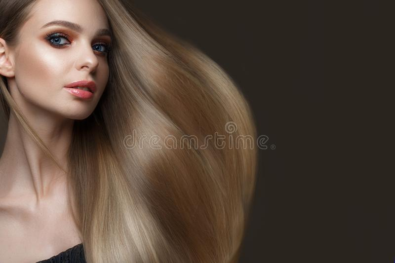 Beautiful blond girl with a perfectly smooth hair, classic make-up. Beauty face royalty free stock image