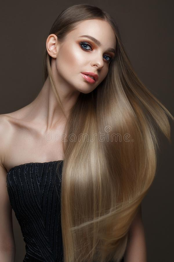 Beautiful blond girl with a perfectly smooth hair, classic make-up. Beauty face stock images