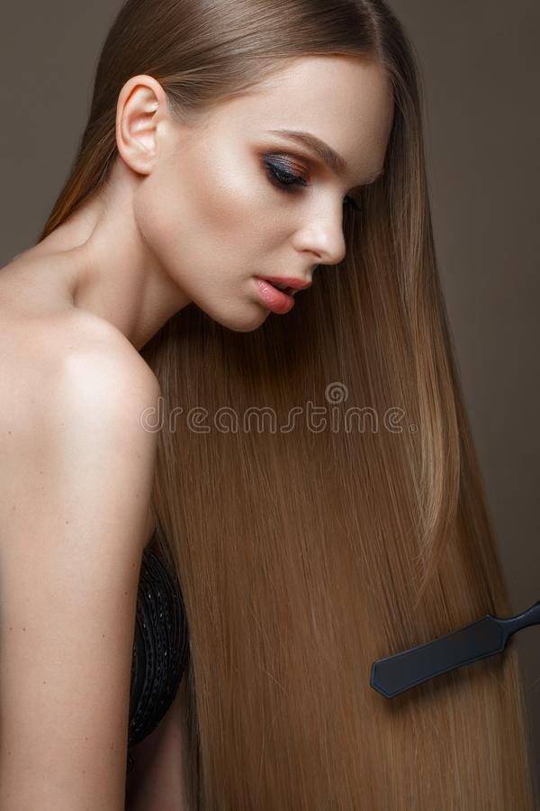 Beautiful blond girl with a perfectly smooth hair, classic make-up. Beauty face royalty free stock photos