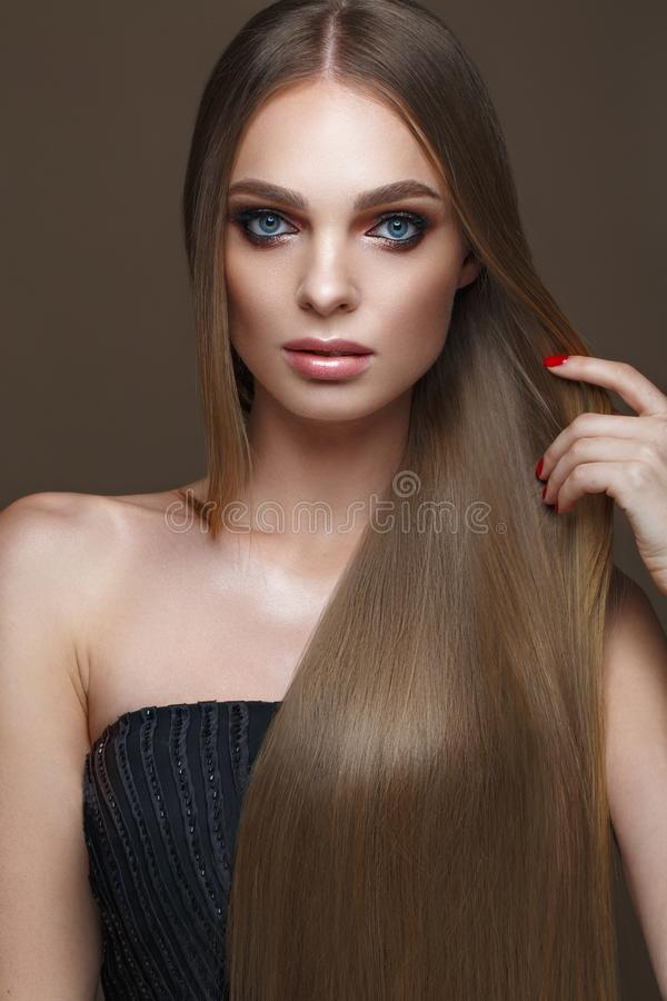 Beautiful blond girl with a perfectly smooth hair, classic make-up. Beauty face stock image
