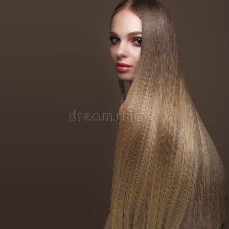Beautiful blond girl with a perfectly smooth hair, classic make-up. Beauty face royalty free stock photo
