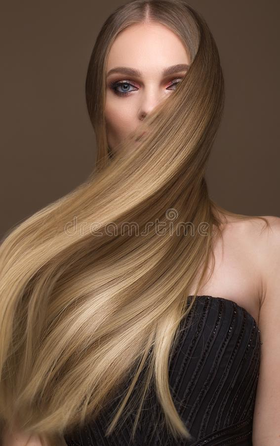 Beautiful blond girl with a perfectly smooth hair, classic make-up. Beauty face stock photos