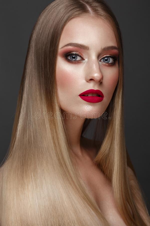 Beautiful blond girl with a perfectly smooth hair, classic make-up and red lips. Beauty face stock images