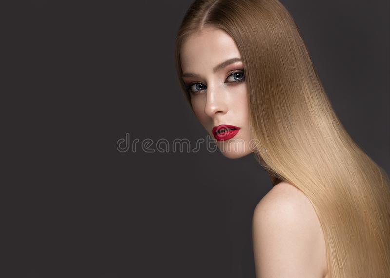 Beautiful blond girl with a perfectly smooth hair, classic make-up and red lips. Beauty face stock photo